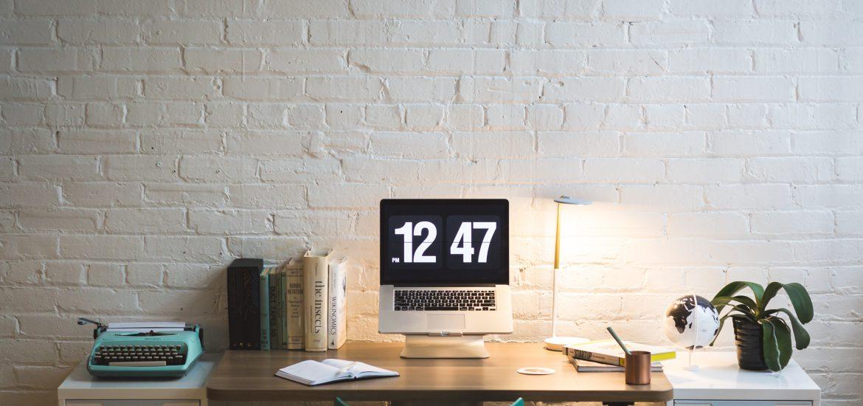 Arbeitsplatz Schreibtisch Offener Rechner mit Zeitangabe